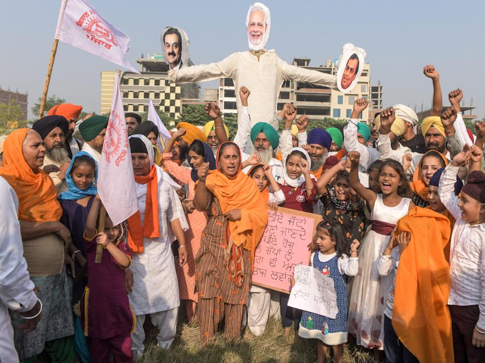 Punjab's farmers burn an effigy of prime minister Narendra Modi as part of protests against new agricultural reforms  (AFP via Getty Images)