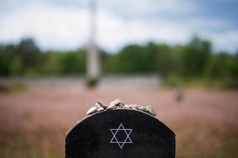 Pebble stones lie on a memorial stone on the grounds of the former Prisoner of War and concentration camps Bergen-Belsen in Bergen, north of Hanover, central Germany, on June 21, 2015 (AFP Photo/Nigel Treblin)