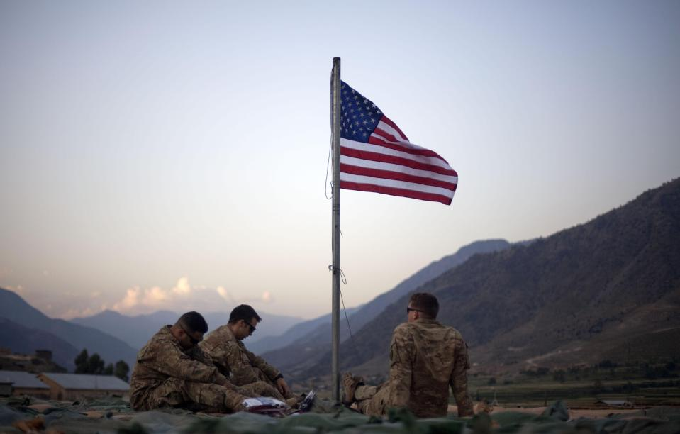FILE - In this Sept. 11, 2011 file photo, US soldiers sit beneath an American flag just raised to commemorate the tenth anniversary of the 9/11 attacks at Forward Operating Base Bostick in Kunar province, Afghanistan. After 20 years of military engagement and billions of dollars spent, NATO and the United States still grapple with the same, seemingly intractable conundrum — how to withdraw troops from Afghanistan without abandoning the country to even more mayhem. (AP Photo/David Goldman, File)
