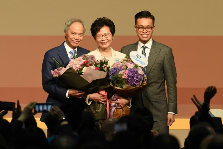 Hong Kong's new chief executive Carrie Lam (C) has pledged to mend political rifts after winning a vote dismissed as a sham by democracy activists