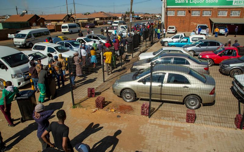 Customers queue to buy alcohol for the first time in two months in Johannesburg -  Themba Hadebe/AP
