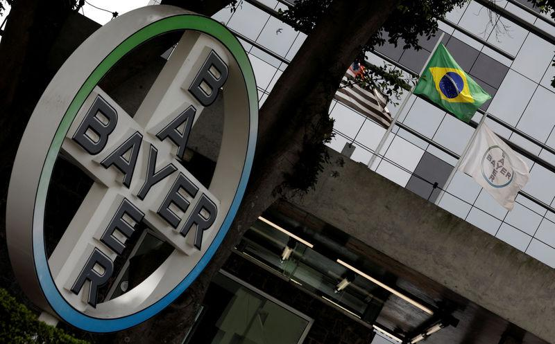 FILE PHOTO: The Brazilian national flag is seen next to Bayer's flag in front of Bayer headquarters in Sao Paulo