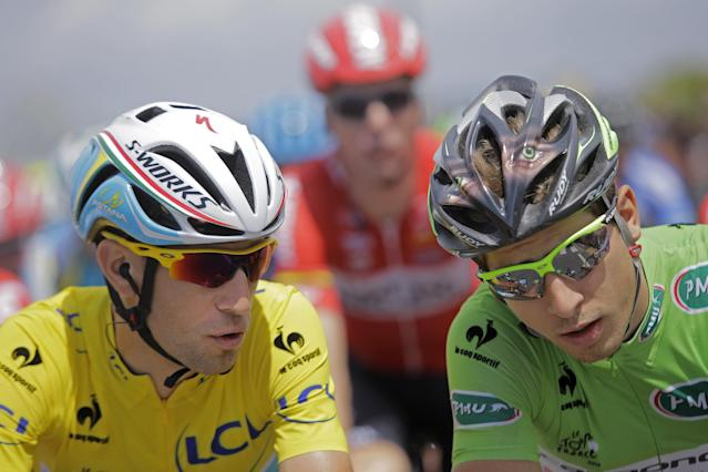 Italy's Vincenzo Nibali, wearing the overall leader's yellow jersey, and Peter Sagan of Slovakia, wearing the best sprinter's green jersey, talk during the ceremonial procession prior to the start of the fourth stage of the Tour de France cycling race over 163.5 kilometers (101.6 miles) with start in Le Touquet and finish in Lille, France, Tuesday, July 8, 2014. (AP Photo/Laurent Cipriani)
