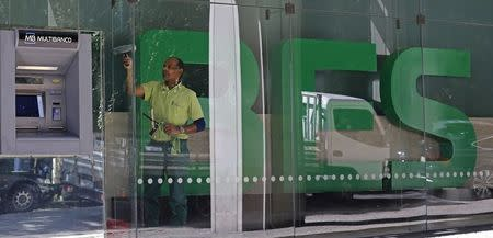 A cleaner cleans the windows of Portuguese bank Banco Espirito Santo (BES) headquarters in downtown Lisbon in this August 5, 2014 file photo. REUTERS/Hugo Correia/Files