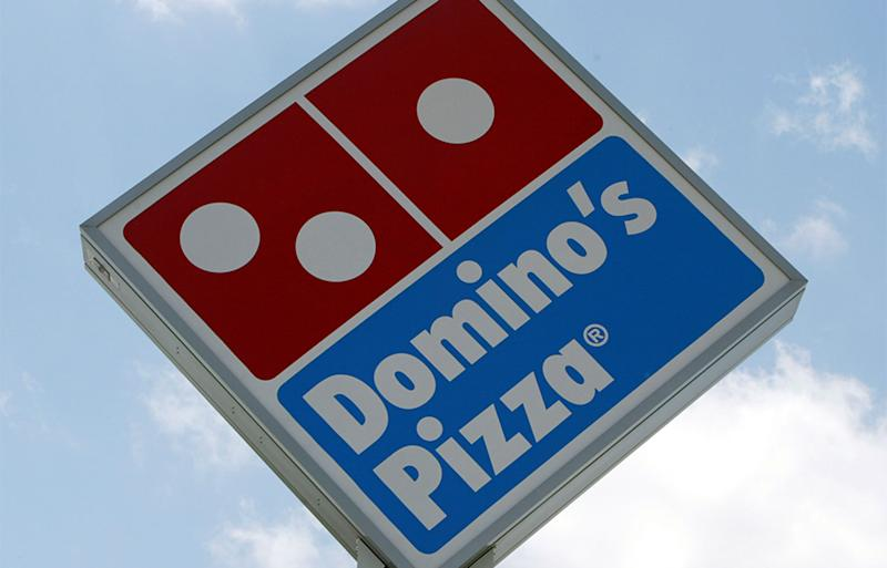 A Domino's pizza logo is seen on a sign on a sunny day.