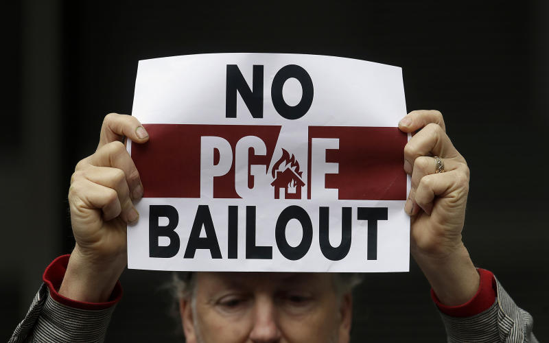 FILE - In this Monday, Jan. 28, 2019 photo, a man holds a sign at a rally before a California Public Utilities Commission meeting in San Francisco.  Pacific Gas & Electric has agreed to pay $11 billion to a group of insurance companies representing most of the claims from Northern California wildfires in 2017 and 2018 as the company tries to emerge from bankruptcy, the utility announced Friday, Sept. 13, 2019.(AP Photo/Jeff Chiu, File)