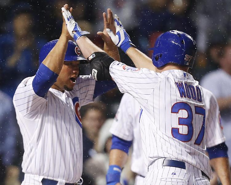 Chicago Cubs' Travis Wood, right, celebrates with Welington Castillo after Wood hit a three-run home run against the Arizona Diamondbacks during the second inning of a baseball game on Monday, April 21, 2014, in Chicago. Castillo scored on the home run. (AP Photo/Andrew A. Nelles)