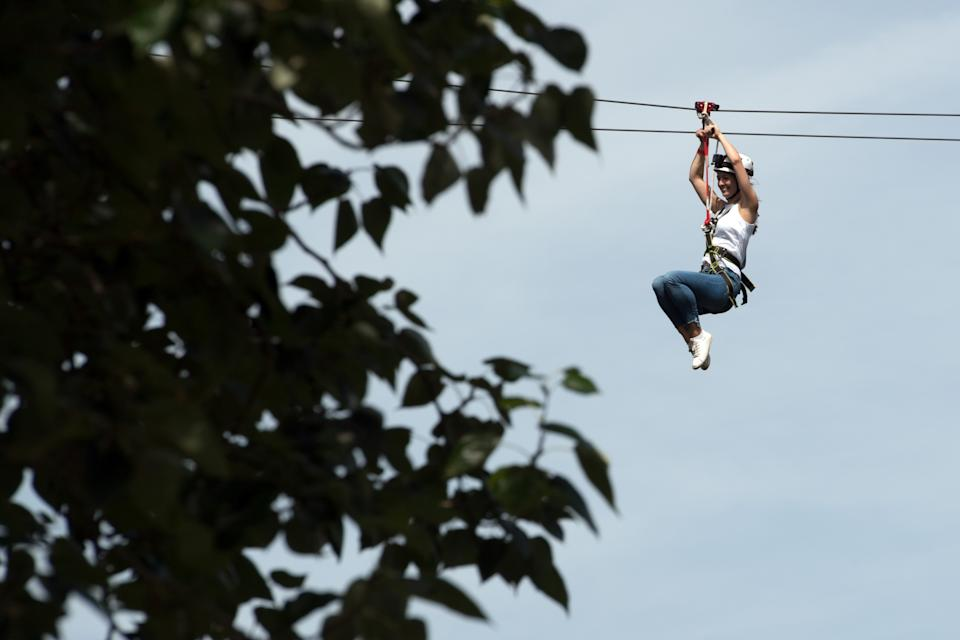 LONDON, ENGLAND - JULY 18:  A woman rides the Zip World zip wire over Archbishop's Park on July 18, 2017 in London, England. The zip wire is 35 metres high at its highest point and 225 metres-long making it the world's biggest and fastest city-centre zip line.  (Photo by Carl Court/Getty Images)