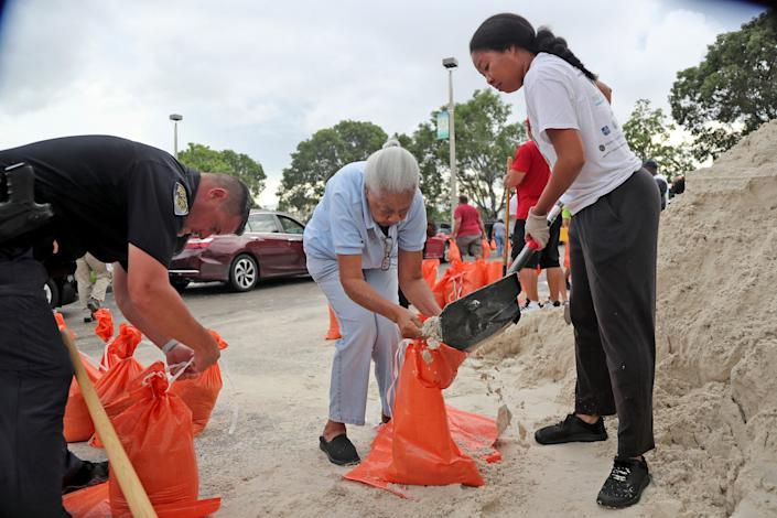 Joan Chang, center, gets help filling her bags during a sandbag giveaway in preparation for Hurricane Dorian, Friday, Aug. 30, 2019, in Margate, Fla.