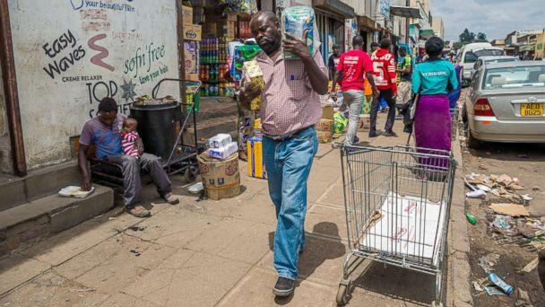 PHOTO: A man carries his wares through a market as business continues in the Zimbabwean capital Harare on Nov. 16, 2017, a day after the military announced plans to arrest 'criminals' close to the president. (AFP/Getty Images)