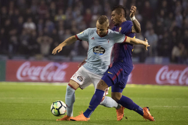 RC Celta's Stanislav Lobotka, left, challenges for the ball with Barcelona's Paulinho during a Spanish La Liga soccer match between RC Celta and Barcelona at the Balaidos stadium in Vigo, Spain, Tuesday April 17, 2018. (AP Photo/Lalo R. Villar)