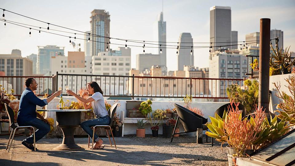 Couple Drinking Wine And Making Toast On Rooftop Terrace With City Skyline In Background.