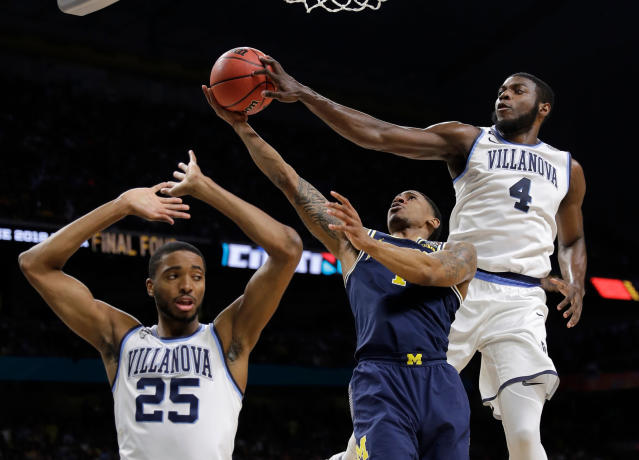 Villanova's Eric Paschall (4) blocks a shot byMichigan's Charles Matthews as Villanova's Mikal Bridges (25) defends during the first half in the championship game of the Final Four NCAA college basketball tournament, Monday, April 2, 2018, in San Antonio. (AP Photo/David J. Phillip)