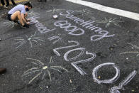 Jolin Polasek draws a sign in chalk on a street in Harlem after former vice president and Democratic presidential candidate Joe Biden was announced as the winner. (AP Photo/Mark Lennihan)