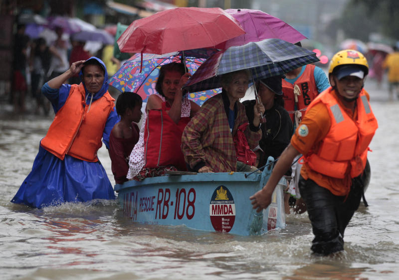 Rescuers pull a boat carrying residents as they enforce evacuation at an area flooded due to a swollen river in Marikina city, east of Manila, Philippines Tuesday, Aug. 20, 2013. Some of the Philippines' heaviest rains on record fell for a second day Tuesday, turning the capital's roads into rivers and trapping tens of thousands of people in homes and shelters. The government suspended all work except rescues and disaster response. (AP Photo/Aaron Favila)