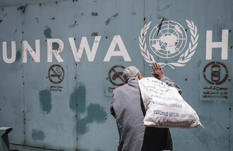 A file picture shows a Palestinian man standing in front of the emblem of the UN agency for Palestinian refugees outside its offices in Gaza City on July 31, 2018 (AFP Photo/SAID KHATIB)