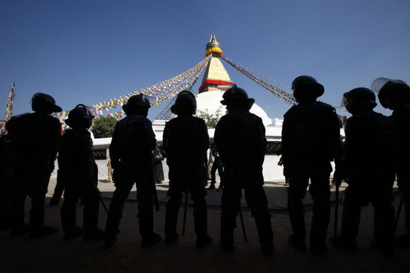 Nepalese policemen stand guard near Boudhanath Stupa during the third day of Tibetan New Year in Katmandu,Nepal, Wednesday, Feb. 13, 2013. A Tibetan protester doused himself with gasoline and set himself on fire in Nepal's capital Wednesday, the latest self-immolation to protest Chinese rule in Tibet. (AP Photo/Niranjan Shrestha)