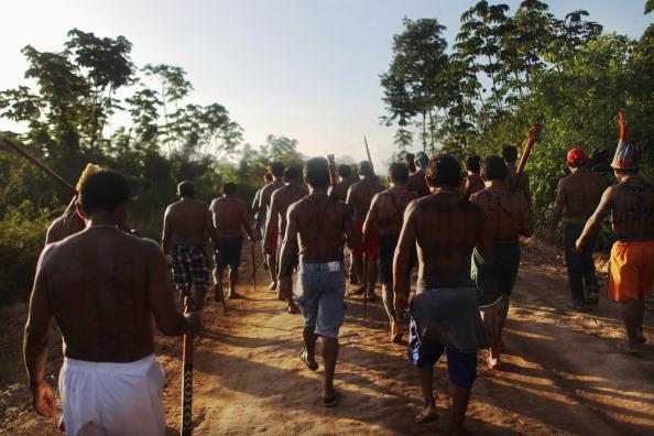 Indigenous people from the Kuruaia and Xipaia tribes march during a ceremony honoring the Xingu River before the start of the Xingu  23 event that gathers resisters of the Belo Monte dam project in the Amazon basin on June 13, 2012 in Santo Antonio, near Altamira, Brazil. Santo Antonio is adjacent to where the Belo Monte dam complex is under construction and the entire community will be expropriated for the construction. Around 60 families originally lived in Santo Antonio but now only about ten families remain. Mario Tama/Getty Images