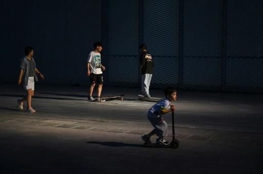 In crowded Shanghai, small children often play in places frequented by skateboarders