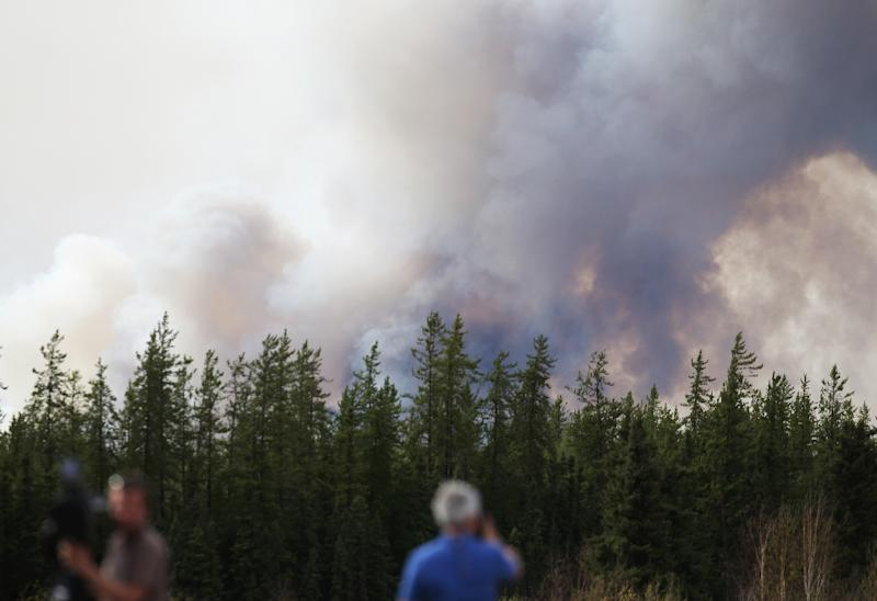 Smoke rises off Highway 63 on May 7, 2016 outside Fort McMurray, where raging forest fires have forced more than 88,000 from their homes