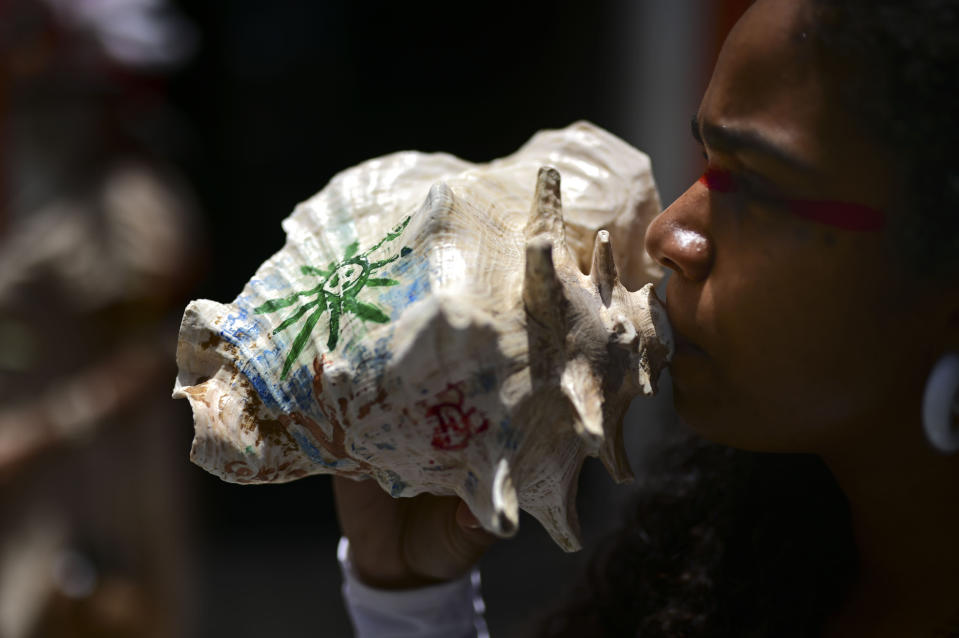 A woman blows on a conch shell as she takes part in a march demanding statues and street names commemorating symbols of colonial oppression be removed, in San Juan, Puerto Rico, Saturday, July 11, 2020. Dozens of activists marched through the historic part of Puerto Rico's capital on Saturday to demand that the U.S. territory's government start by removing statues, including those of explorer Christopher Columbus. (AP Photo/Carlos Giusti)