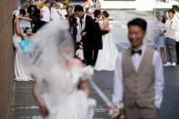Couples prepare to get their photo taken during a wedding photography shoot, amid the coronavirus disease pandemic, in Shanghai