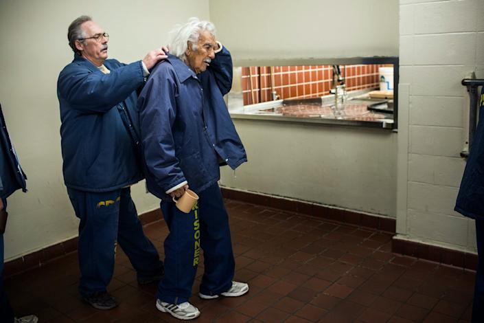 """<span class=""""caption"""">An 82-year-old prisoner being assisted on the breakfast line at California Men's Colony prison.</span> <span class=""""attribution""""><a class=""""link rapid-noclick-resp"""" href=""""https://www.gettyimages.com/detail/news-photo/anthony-alvarez-age-82-waits-in-line-for-breakfast-while-news-photo/458007541?adppopup=true"""" rel=""""nofollow noopener"""" target=""""_blank"""" data-ylk=""""slk:Andrew Burton/Getty Images"""">Andrew Burton/Getty Images</a></span>"""