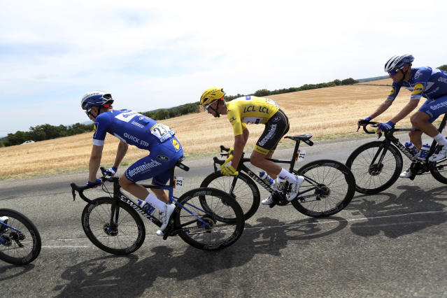 France's Julian Alaphilippe wearing the overall leader's yellow jersey, center, rides with Belgium's Dries Devenyns, left, during the eleventh stage of the Tour de France cycling race over 167 kilometers (103,77 miles) with start in Albi and finish in Toulouse, France, Wednesday, July 17, 2019. (AP Photo/Thibault Camus)