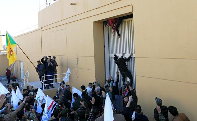 Hashd al-Shaabi (paramilitary forces) fighters try to enter the U.S. Embassy in Baghdad on Dec. 31 during a protest to condemn airstrikes on their bases. (Photo: Thaier al-Sudani /Reuters)