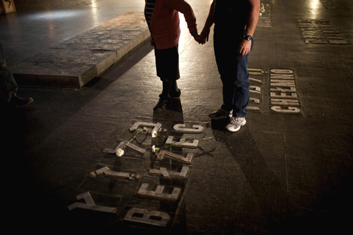 Relatives of Holocaust victims lay flowers next to the names of concentration camps during a ceremony marking the annual Holocaust Remembrance Day at the Yad Vashem Holocaust Memorial in Jerusalem, Monday, April 8, 2013. Israel came to a standstill for two mournful minutes Monday as sirens pierced the air in an annual ritual to remember the 6 million Jews systematically murdered by German Nazis and their collaborators during the Holocaust in World War II. (AP Photo/Oded Balilty)