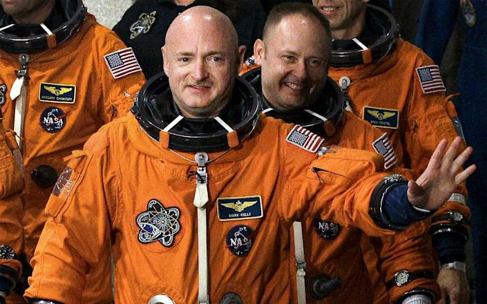 In this May 16, 2011, file photo, former NASA astronaut STS-134 commander Mark Kelly, front, waves a he leaves the Operations and Checkout Building with fellow crew members, including Mike Fincke, for a trip to Launch Pad 39-A, and a planned liftoff on the space shuttle Endeavour at Kennedy Space Center in Cape Canaveral, Fl - Chris O'Meara/AP