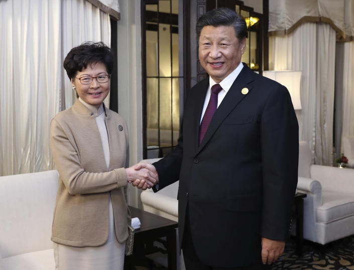 In this Monday, Nov. 4, 2019, file photo released by China's Xinhua News Agency, Chinese President Xi Jinping poses with Hong Kong Chief Executive Carrie Lam for a photo during a meeting in Shanghai, China. Lam is here for the second China International Import Expo (CIIE). (Ju Peng/Xinhua via AP, File)