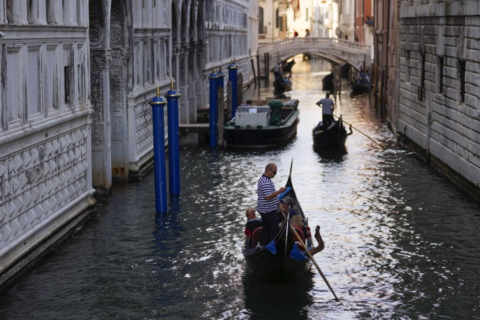 Gondoliers take tourists by the Ponte dei Sospiri (Bridge of Sighs), in Venice, Italy, Thursday, June 17, 2021. After a 15-month pause in mass international travel, Venetians are contemplating how to welcome visitors back to the picture-postcard canals and Byzantine backdrops without suffering the indignities of crowds clogging its narrow alleyways, day-trippers perched on stoops to imbibe a panino and hordes of selfie-takers straining for a spot on the Rialto Bridge or in front of St. Mark's Basilica. (AP Photo/Luca Bruno)