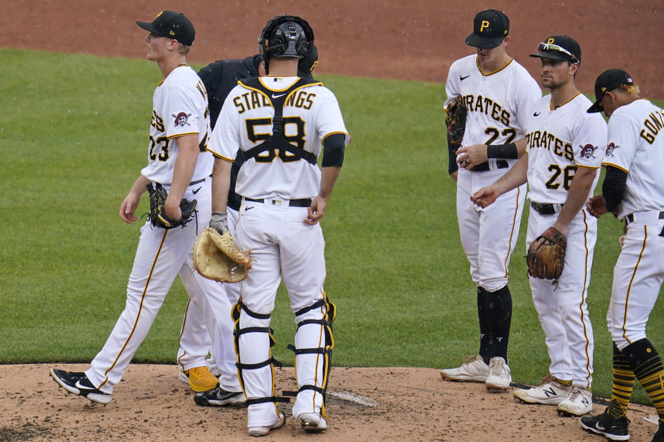 Pittsburgh Pirates starting pitcher Mitch Keller, left, walks off the mound after handing the ball to manager Derek Shelton, rear, during the third inning of a baseball game against the Los Angeles Dodgers in Pittsburgh, Thursday, June 10, 2021. (AP Photo/Gene J. Puskar)