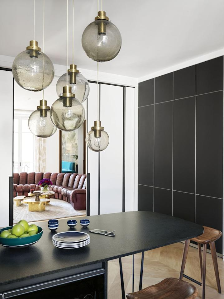 """<p>Design duo <a href=""""https://leberrevevaud.com/"""" target=""""_blank"""">Le Berre Vevaud</a> purchased a cluster of 1950s blown-glass Lustre globes at auction from Piasa, melding modern aesthetics with the luxurious past. The globes are hung over a peninsula of Zimbabwe granite and """"Tractor"""" stools from <a href=""""http://bassamfellows.com/"""" target=""""_blank"""">BassamFellows</a>.</p><p><a class=""""body-btn-link"""" href=""""https://www.piasa.fr/en/home"""" target=""""_blank"""">Shop Now</a></p>"""