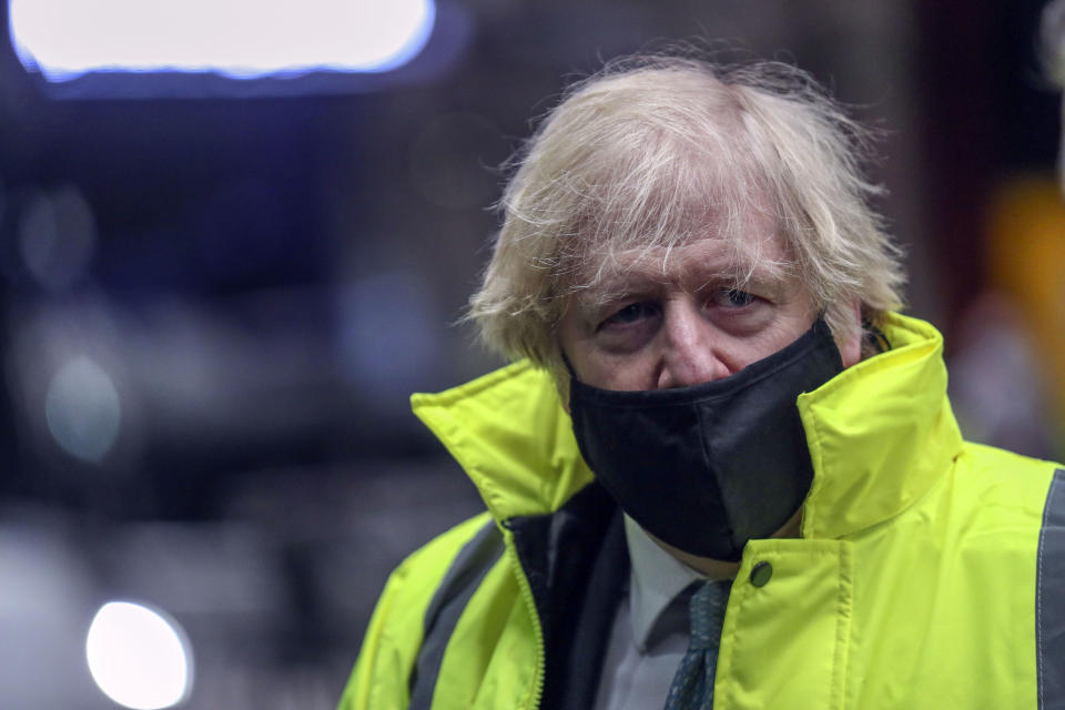Britain's Prime Minister Boris Johnson visits the National Express depot in Coventry, central England, Monday March 15, 2021. The Prime Minister is unveiling a shake-up of the bus sector which aims to see lower, simpler flat fares in towns and cities. (Steve Parsons/Pool via AP)