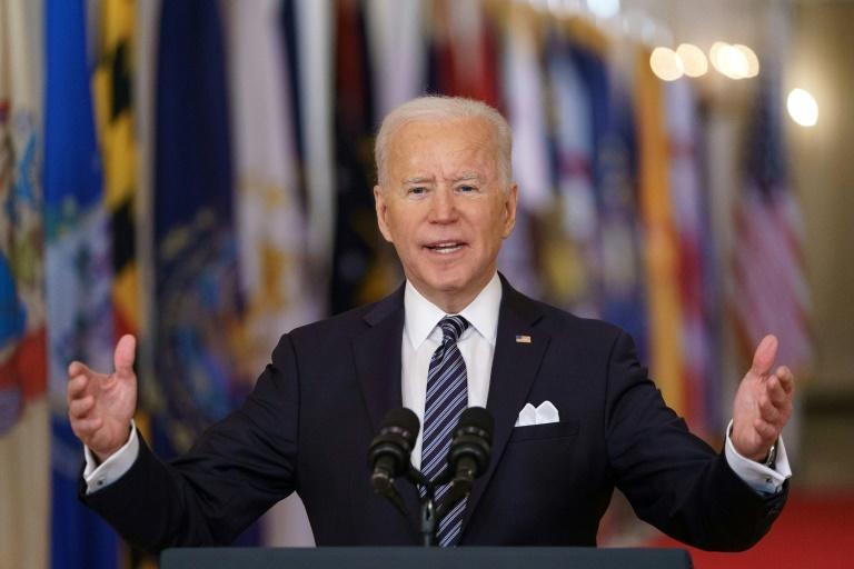 US President Joe Biden gestures as he speaks on the anniversary of the start of the Covid-19 pandemic