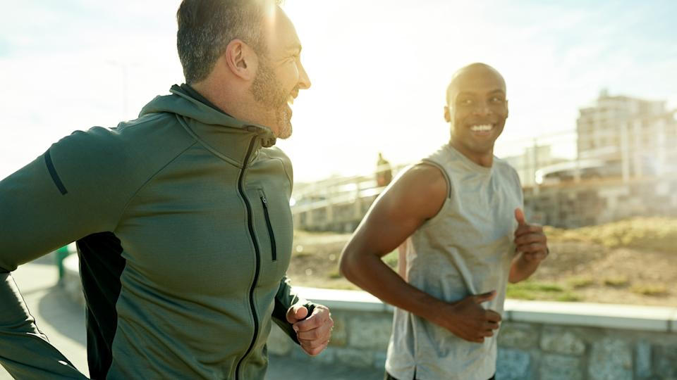 Shot of two sporty men exercising together outdoors.