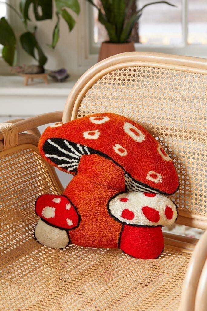 """To bring the forest inside, you might just pop this kitschy mushroom-shaped pillow on an armchair. <a href=""""https://fave.co/3kdxDMx"""" target=""""_blank"""" rel=""""noopener noreferrer"""">Find it for $49 at Urban Outfitters</a>."""