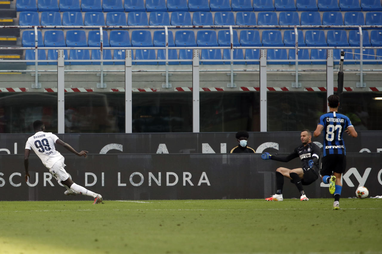 Bologna's Musa Barrow, left, scores his side's second goal during the Serie A soccer match between Inter Milan and Bologna at the Milan San Siro Stadium, Italy, Sunday, July 5, 2020. (AP Photo/Antonio Calanni)