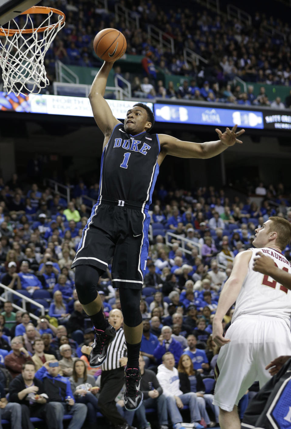 Duke's Jabari Parker (1) sails past Elon's Ryley Beaumont (21) for a dunk during the first half of an NCAA college basketball game in Greensboro, N.C., Tuesday, Dec. 31, 2013. (AP Photo/Chuck Burton)