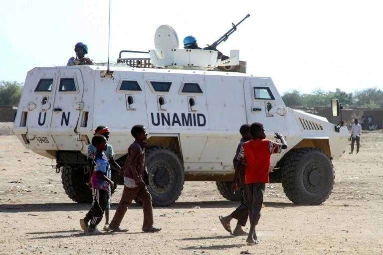 Sudanese children walk past an armoured vehicle of the United Nations and African Union peacekeeping mission (UNAMID) in Kalma Camp for internally displaced people in Nyala, the capital of South Darfur, on Wednesday
