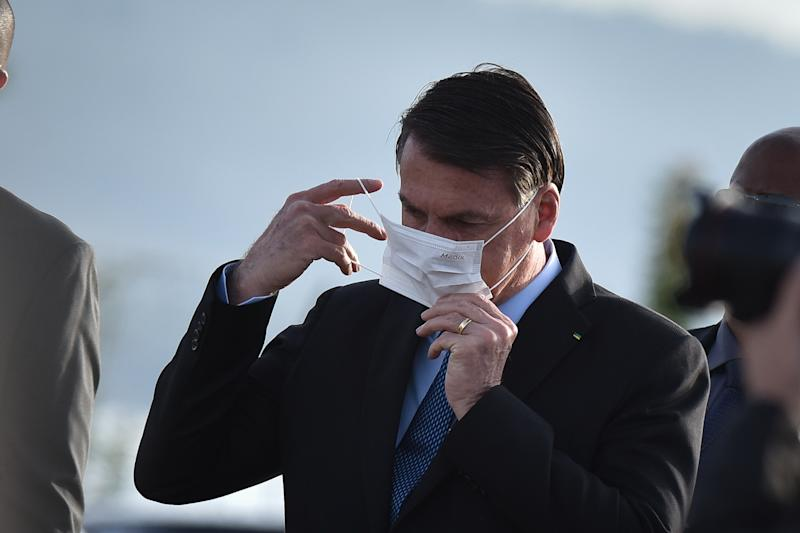 Brazil's president Jair Bolsonaro wears a face mask when arrives for the National Flag Raising ceremony in front of Alvorada Palace amid the Coronavirus (COVID-19) pandemic, in Brasilia, Brazil, on Tuesday, June 9, 2020. (Photo by Andre Borges/NurPhoto via Getty Images)