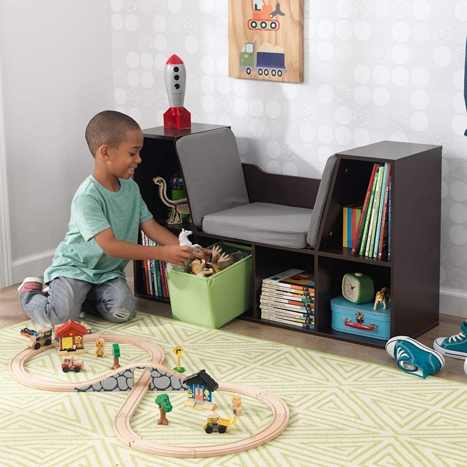 """Save some floor space and give your kiddo's room a totally personalized touch at the same time when you put this in their room.<br /><br /><strong>Promising review:</strong>""""This took about an hour and 15 minutes to assemble, which is great considering I'm really not a handy person. The lower cubicles are quite short, which did impose a limit on which books we could put in, but the upper two are taller so it all worked out. It's quite sturdy and my kids are really excited to sit on it and read!"""" — <a href=""""https://www.amazon.com/gp/customer-reviews/R3CKZ0W5ZFAMRW?&linkCode=ll2&tag=huffpost-bfsyndication-20&linkId=0ba55177fb07d3cf3ed8f483007e21fa&language=en_US&ref_=as_li_ss_tl"""" target=""""_blank"""" rel=""""nofollow noopener noreferrer"""" data-skimlinks-tracking=""""5854435"""" data-vars-affiliate=""""Amazon"""" data-vars-href=""""https://www.amazon.com/gp/customer-reviews/R3CKZ0W5ZFAMRW?tag=bfmal-20&ascsubtag=5854435%2C17%2C37%2Cmobile_web%2C0%2C0%2C16324248"""" data-vars-keywords=""""cleaning,fast fashion"""" data-vars-link-id=""""16324248"""" data-vars-price="""""""" data-vars-product-id=""""20942650"""" data-vars-product-img="""""""" data-vars-product-title="""""""" data-vars-retailers=""""Amazon"""">CBIsrael<br /><br /></a><strong>Get it from Amazon for<a href=""""https://www.amazon.com/KidKraft-Bookcase-Reading-Nook-White/dp/B00W610EZC?&linkCode=ll1&tag=huffpost-bfsyndication-20&linkId=6875f83810fcab0df85af81b7c7893f5&language=en_US&ref_=as_li_ss_tl"""" target=""""_blank"""" rel=""""nofollow noopener noreferrer"""" data-skimlinks-tracking=""""5854435"""" data-vars-affiliate=""""Amazon"""" data-vars-asin=""""B00W610EZC"""" data-vars-href=""""https://www.amazon.com/dp/B00W610EZC?tag=bfmal-20&ascsubtag=5854435%2C17%2C37%2Cmobile_web%2C0%2C0%2C16323360"""" data-vars-keywords=""""cleaning,fast fashion"""" data-vars-link-id=""""16323360"""" data-vars-price="""""""" data-vars-product-id=""""18093808"""" data-vars-product-img=""""https://m.media-amazon.com/images/I/31QAp92UVEL.jpg"""" data-vars-product-title=""""KidKraft KKR14230 Bookcase with Reading Nook Toy, White, 46.46"""" x 15.16"""" x 5.04"""""""" data-vars-retailer"""