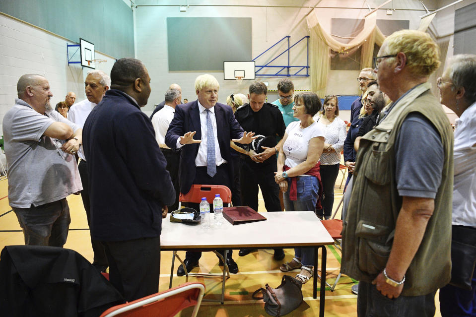 """Britain's Prime Minister Boris Johnson meets with rescue crews and local residents during a visit to Chapel-en-le-Frith High School near the village of Whaley Bridge in Derbyshire, England, Friday, Aug. 2, 2019. A British military helicopter dropped sandbags Friday to shore up a reservoir wall as emergency services worked frantically to prevent a rain-damaged dam from collapsing. Engineers said they remain """"very concerned"""" about the integrity of the 19th-century Toddbrook Reservoir, which contains around 1.3 million metric tons (1.5 million (U.S tons) of water. (Leon Neal/Pool photo via AP)"""