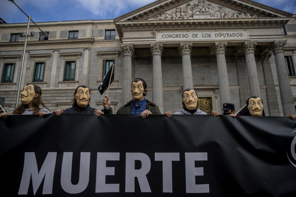 """People hold a banner reading in Spanish """"Death"""" as they protest against a law to legalize euthanasia, in front of the Spanish Parliament in Madrid, Spain, Thursday, Dec. 17, 2020. The Spanish Parliament debates on votes on a bill to legalize euthanasia for those people suffering """"unbearably"""" from a chronic or incurable disease. (AP Photo/Manu Fernandez)"""