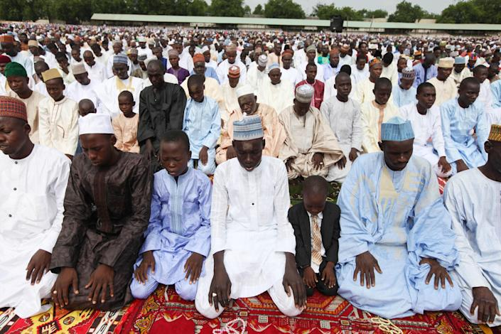 """Nigeria muslims offer their prayers during Eid al-Fitr at Ramat square in Maiduguri, northeastern Nigeria, Thursday, Aug. 8, 2013. Nigerians in the birthplace of an Islamic uprising gripping the northeast Thursday celebrated the Muslim holy day of Eid al-Fitr with devout prayers and a joyful show of adulation for their king that attracted more than 10,000 people. It was the first durbar in three years in the city of Maiduguri and the joy that it could take place _ albeit amid massive security _ was heard in the cries of ululating women, screams of delight from children and men chanting """"Long live the king!"""" (AP Photo/Sunday Alamba)"""