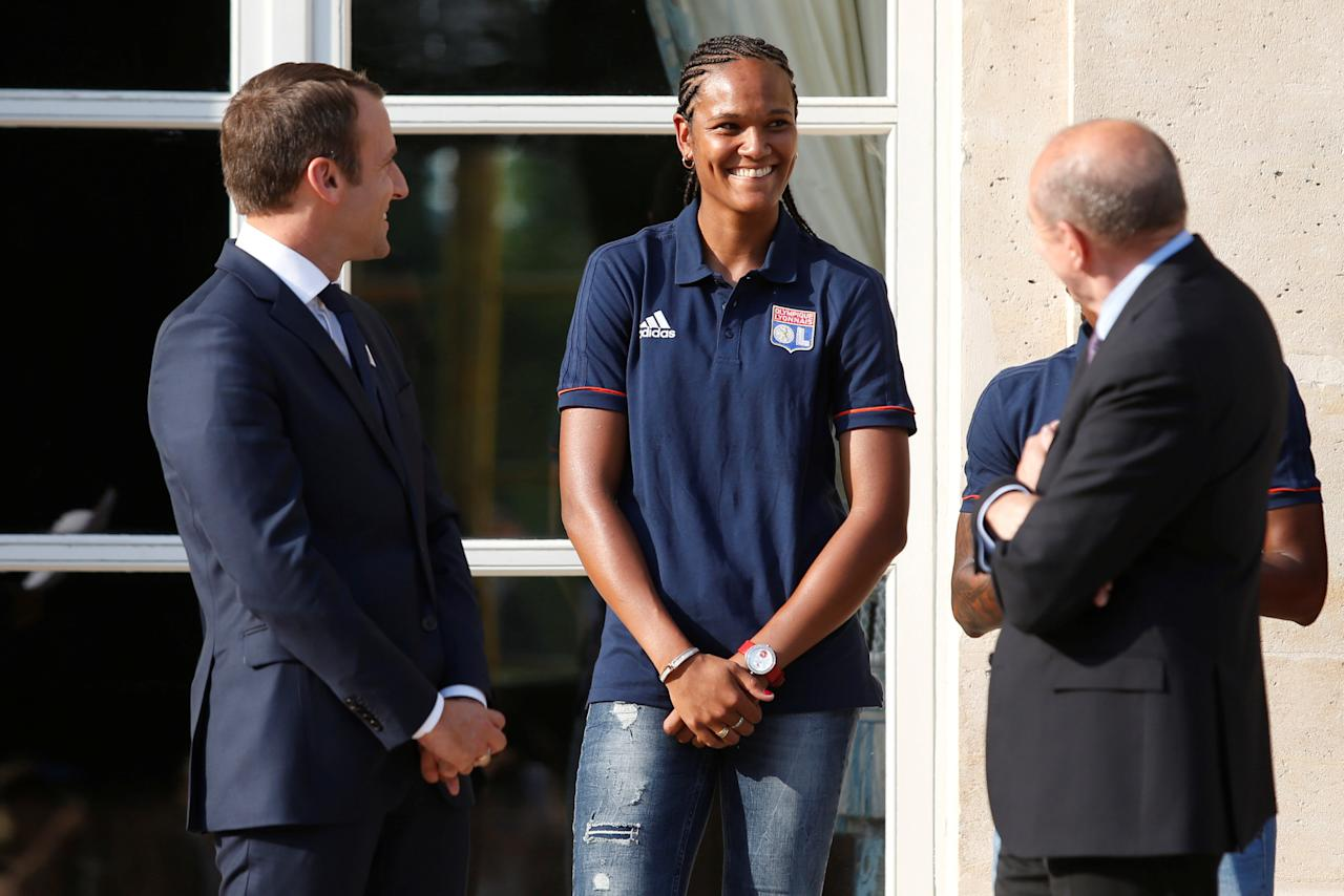 French President Emmanuel Macron (L) and French Interior Minister Gerard Collomb (R) speak to Lyon's French captain Wendie Renard (C) during a ceremony at the Elysee Palace in Paris, France, June 20, 2017 to celebrate the victory of Lyon's football team during the UEFA Women's Champions League.  Picture taken June 20, 2017.    REUTERS/Geoffroy van der Hasselt/Pool