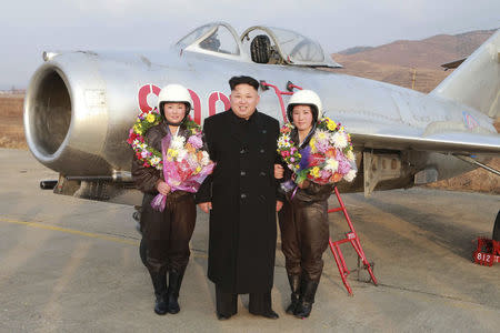 North Korean leader Kim Jong Un poses for pictures with pilots as he provides field guidance to the flight drill of female pilots of pursuit planes of the KPA Air and Anti-Air Force