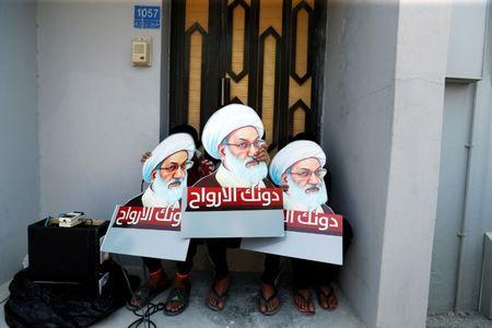 Protesters holding placards with images of Bahrain's leading Shi'ite cleric Isa Qassim, shout religious slogans during an anti-government protest after Friday prayers in the village of Diraz, west of Manama